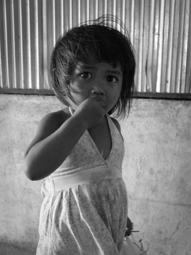 The cute little girl who offered me her rambutan fruit - as you can see she is eating the fruit here...